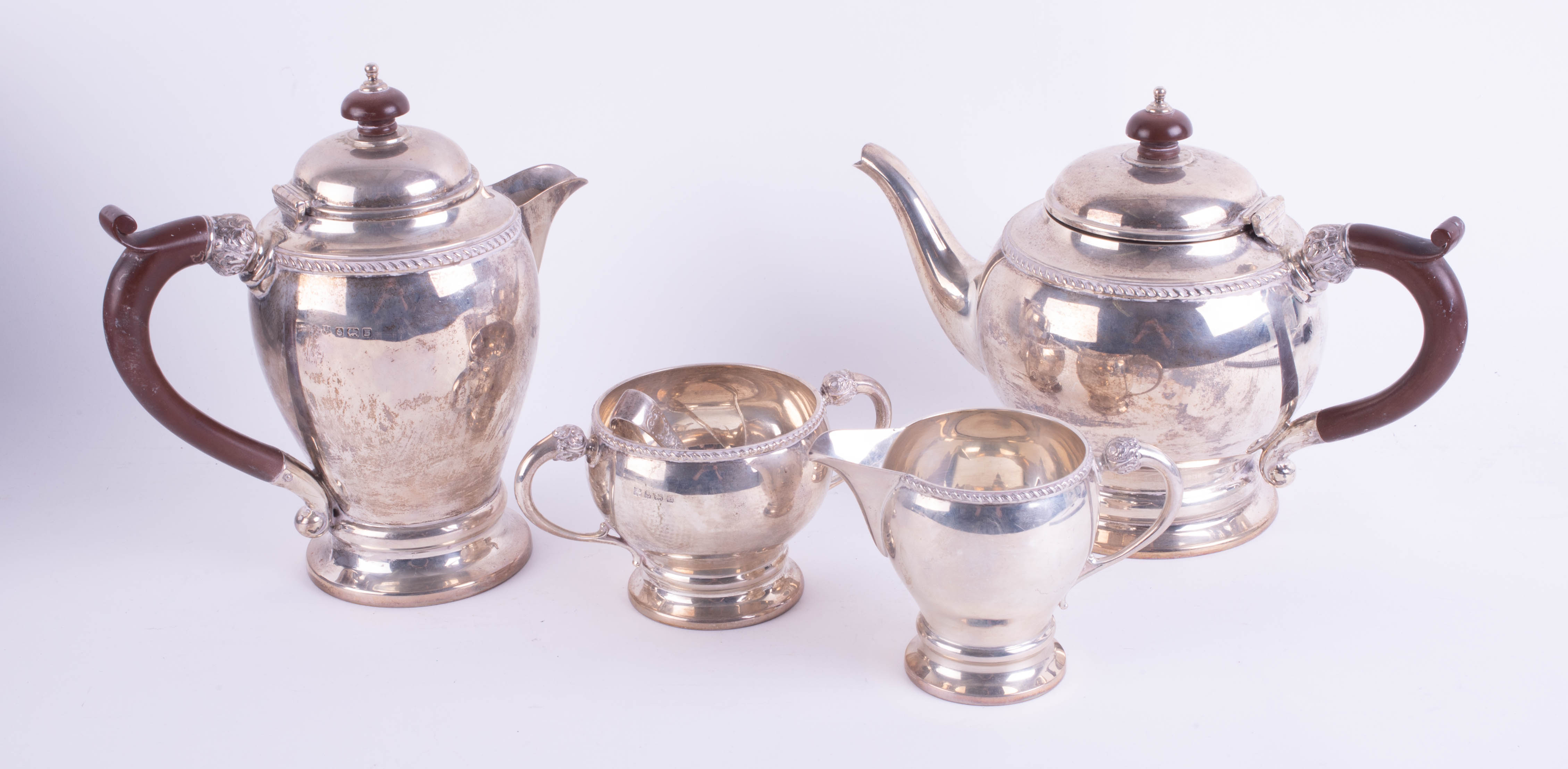 Lot 021 - A Geo V silver four piece tea service together with a pair of silver sugar tongs, total weight
