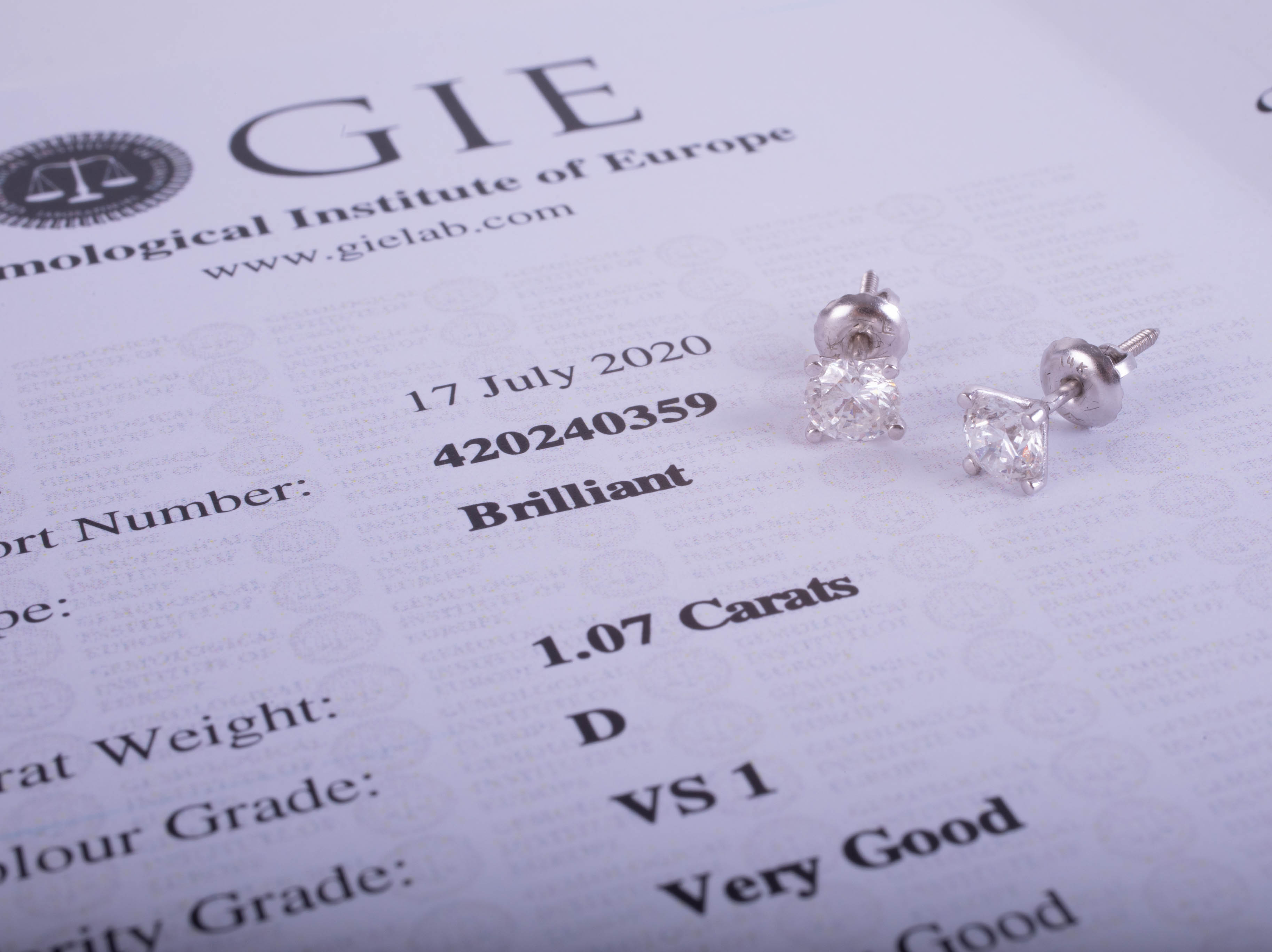 Lot 027 - A pair of diamond earrings, with G.I.E. certificate indicating total carat weight 1.07cts, colour D,