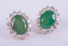A large pair of 18ct yellow gold emerald and diamond cluster stud earrings, boxed, emerald weight