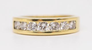 An 18ct diamond eternity ring, half band set with a channel row of seven diamonds, size P.