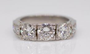 A fine diamond three stone ring, an illusion setting, with three round cut diamonds, the centre