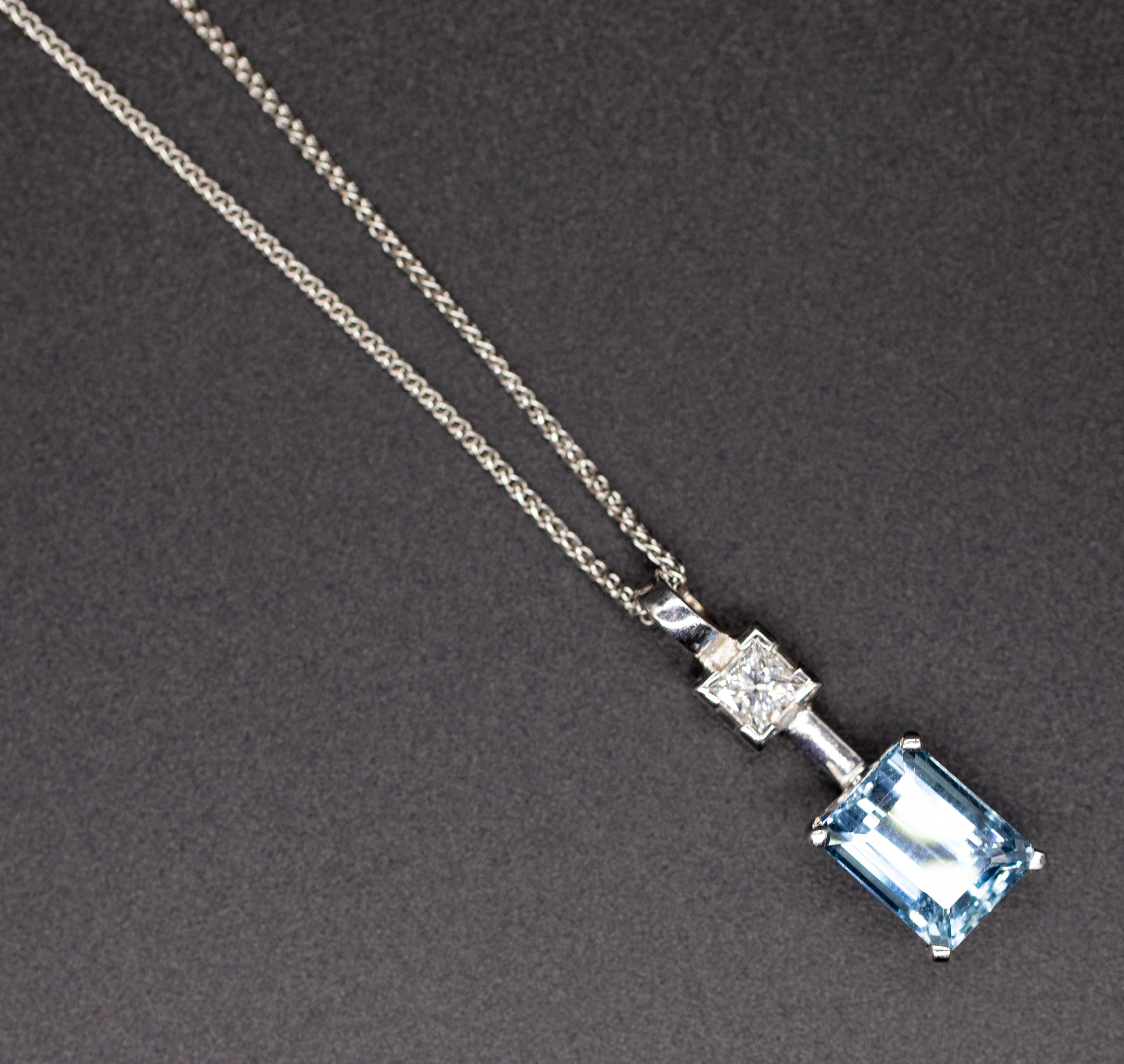 An 18ct aquamarine and diamond set pendant in white gold, on fine chain.