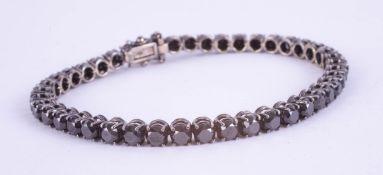 An 18ct white gold black diamond line bracelet, boxed, diamond weight approx 14.38ct.
