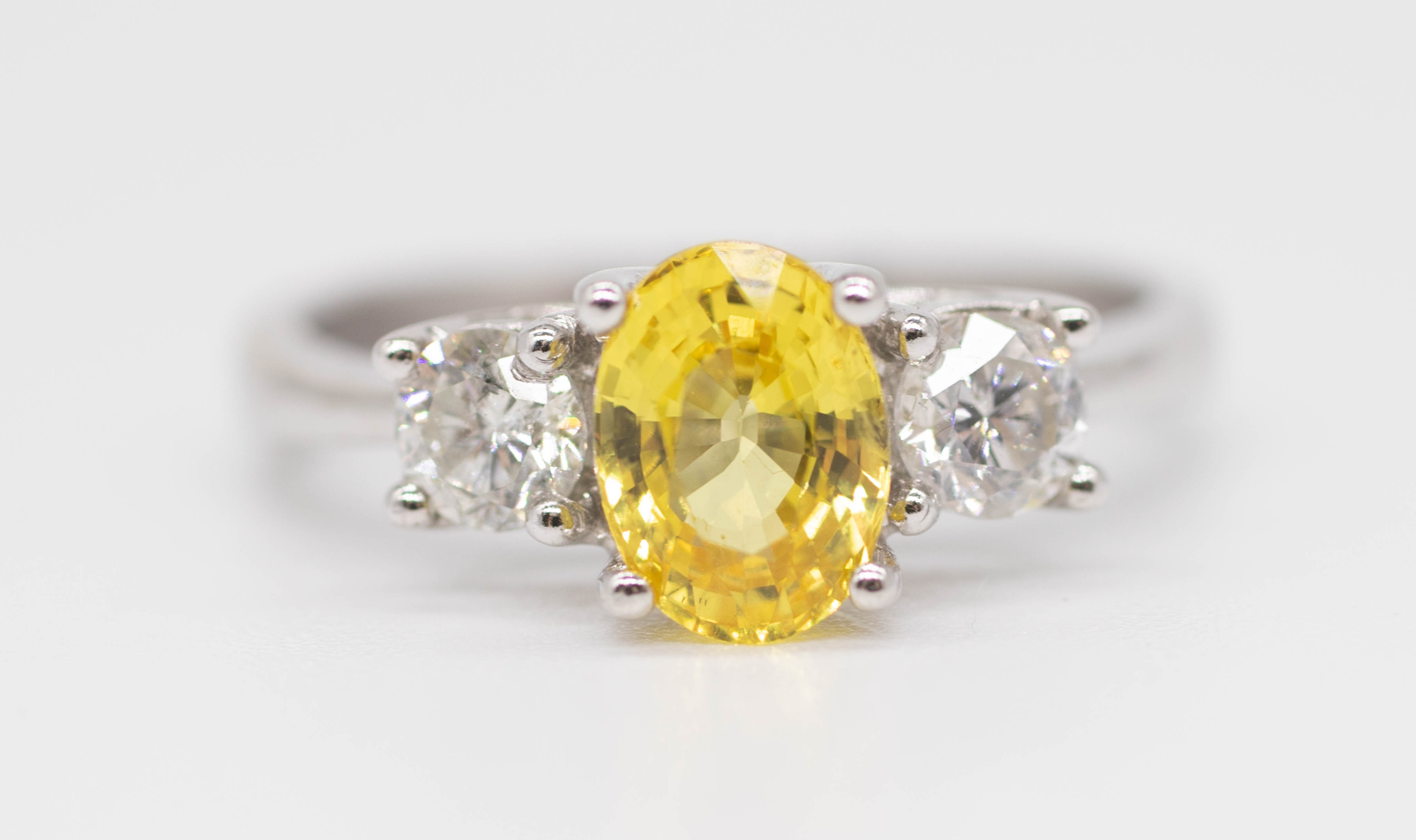 An 18ct yellow sapphire and diamond set three stone ring, size L.
