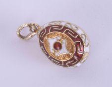An enamel and silver egg pendant, diameter 13mm.
