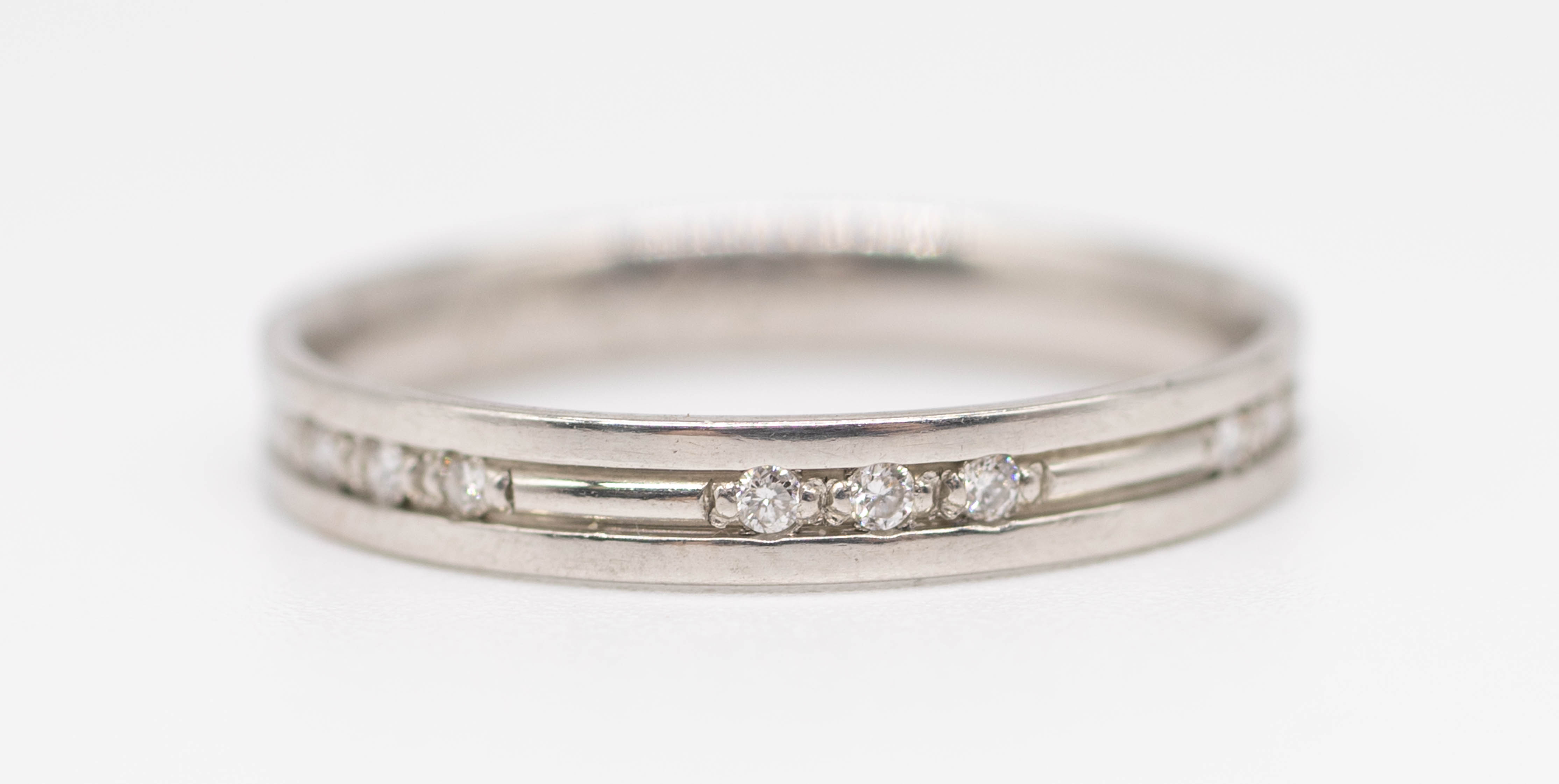 A platinum and diamond set band ring, size N.