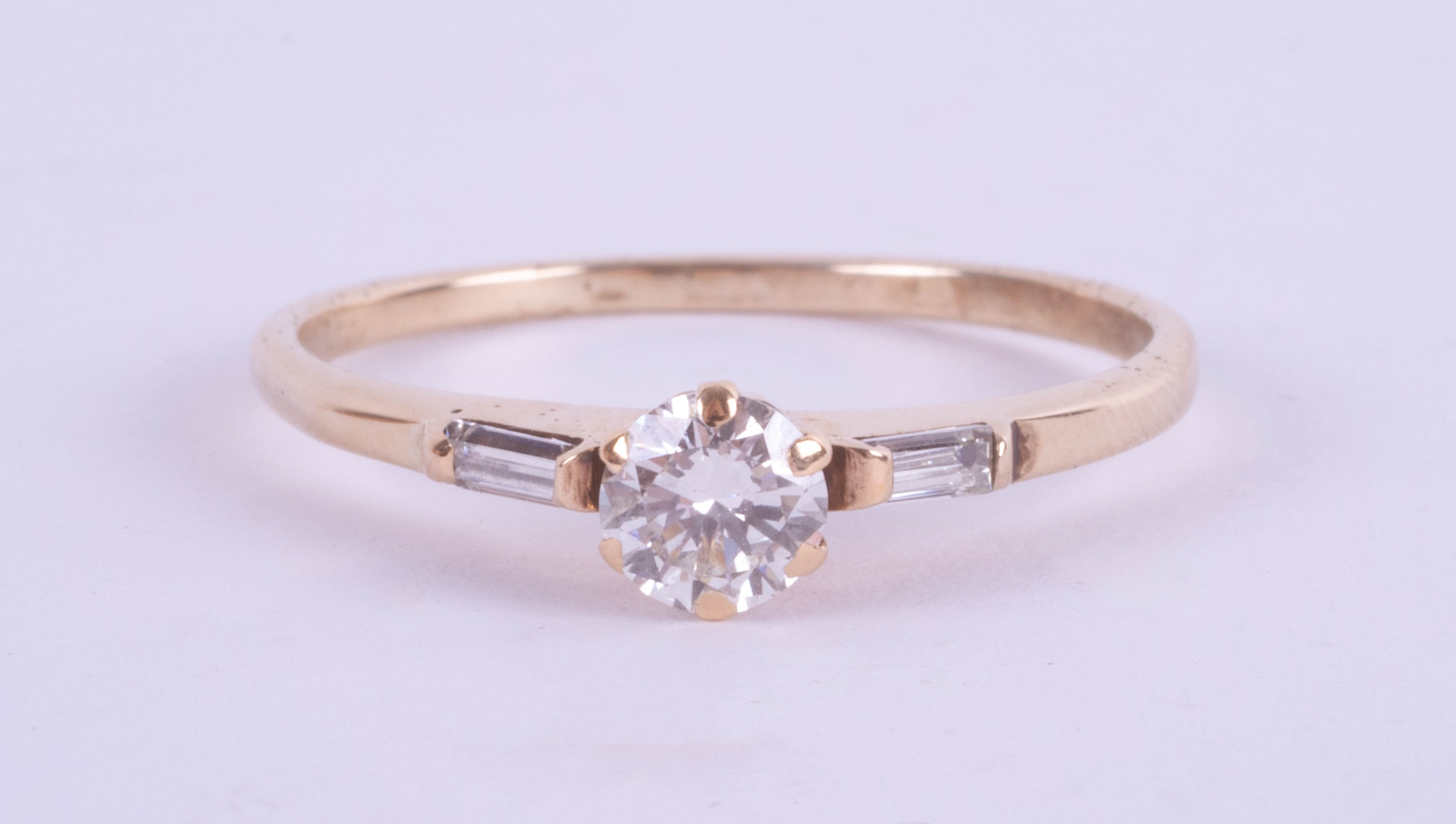An 18ct yellow gold diamond ring set with further diamonds to the shoulders, approx. 0.50ct, ring