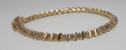 A diamond bracelet set in 10ct yellow gold, length 18cm.