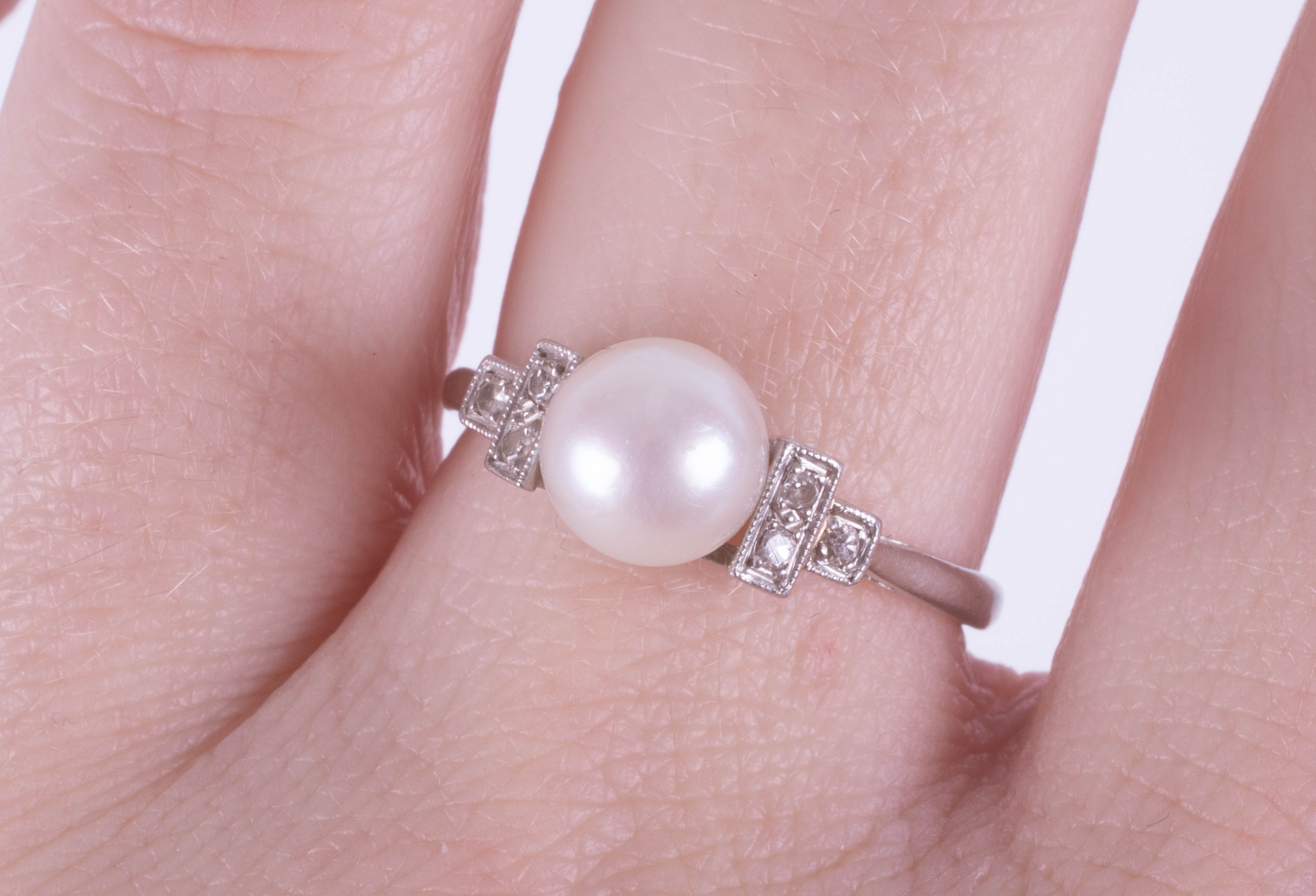 A platinum ring set with a single pearl and diamonds, size O. - Image 2 of 2