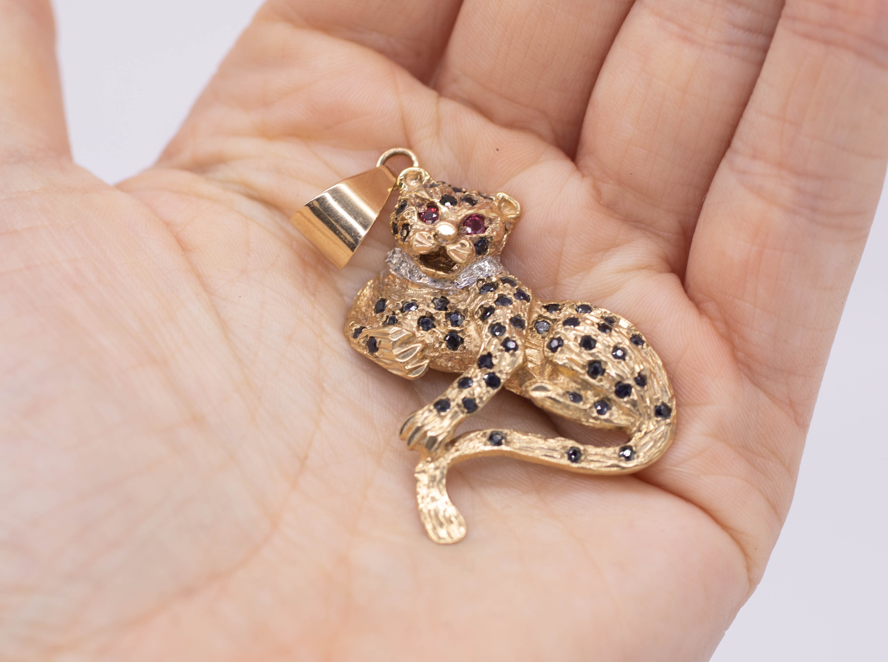 A diamond and sapphire set leopard pendant with ruby eyes, width approximately 35mm.
