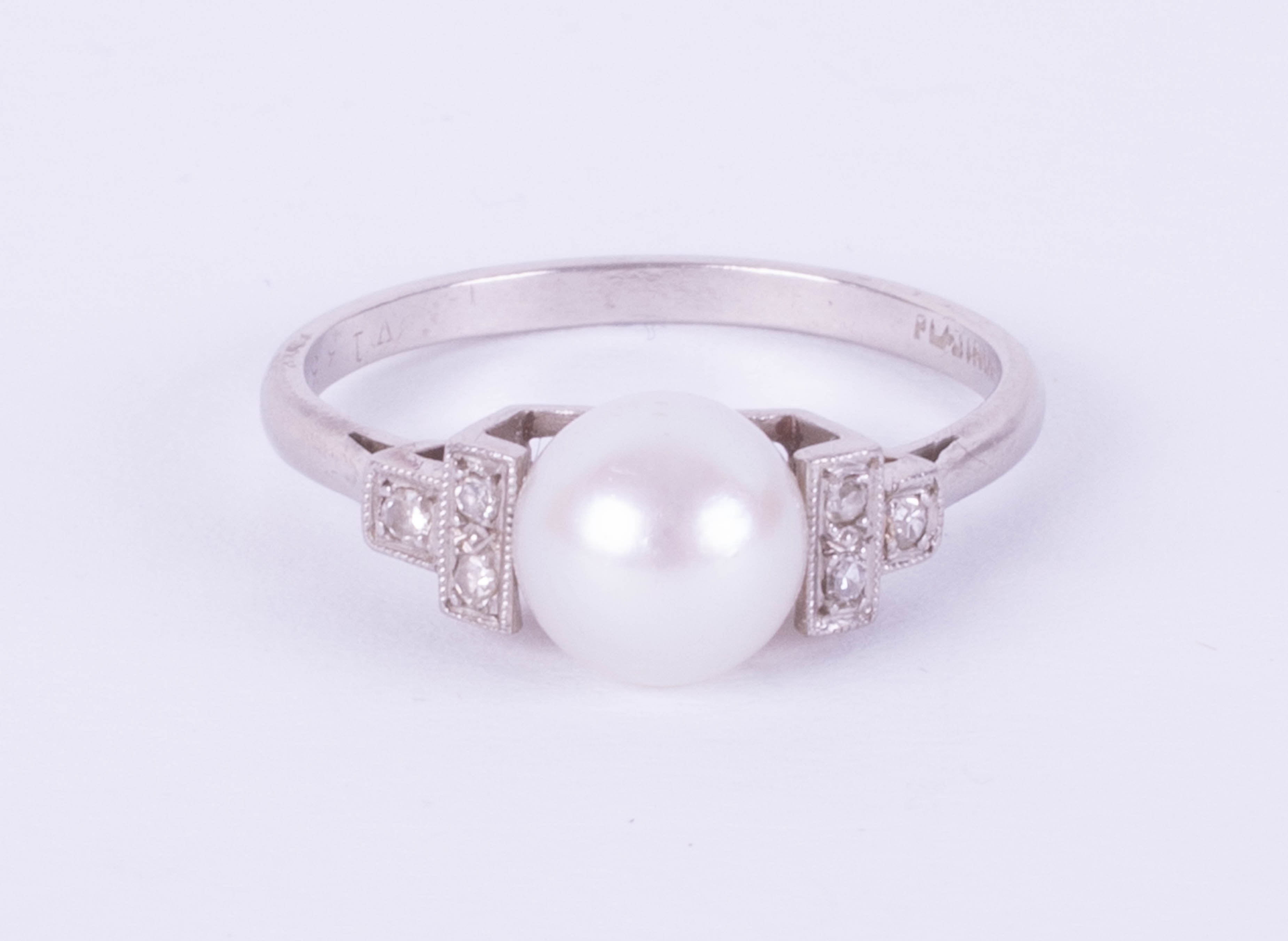 A platinum ring set with a single pearl and diamonds, size O.
