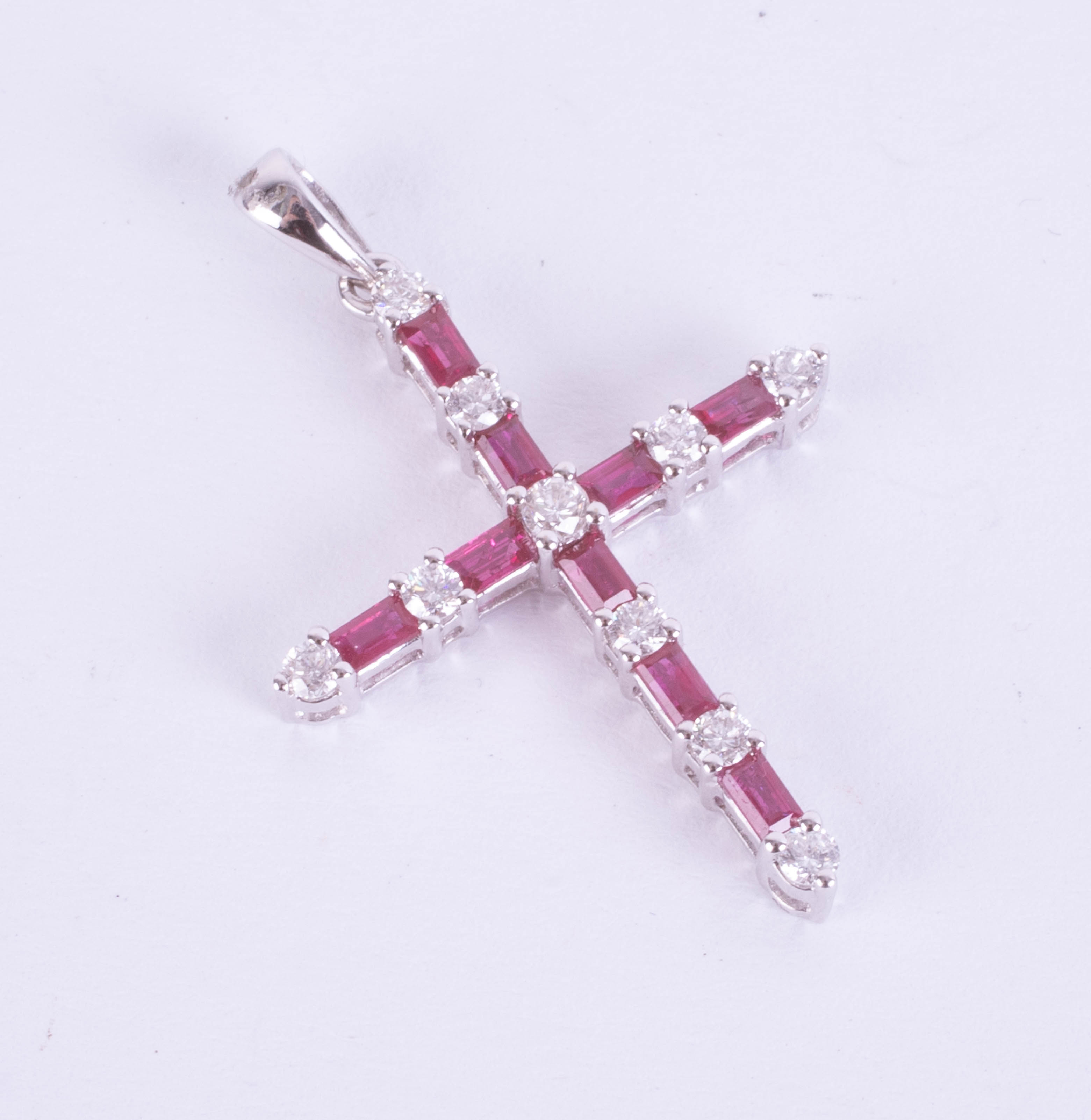 An 18ct white gold ruby and diamond cross pendant.