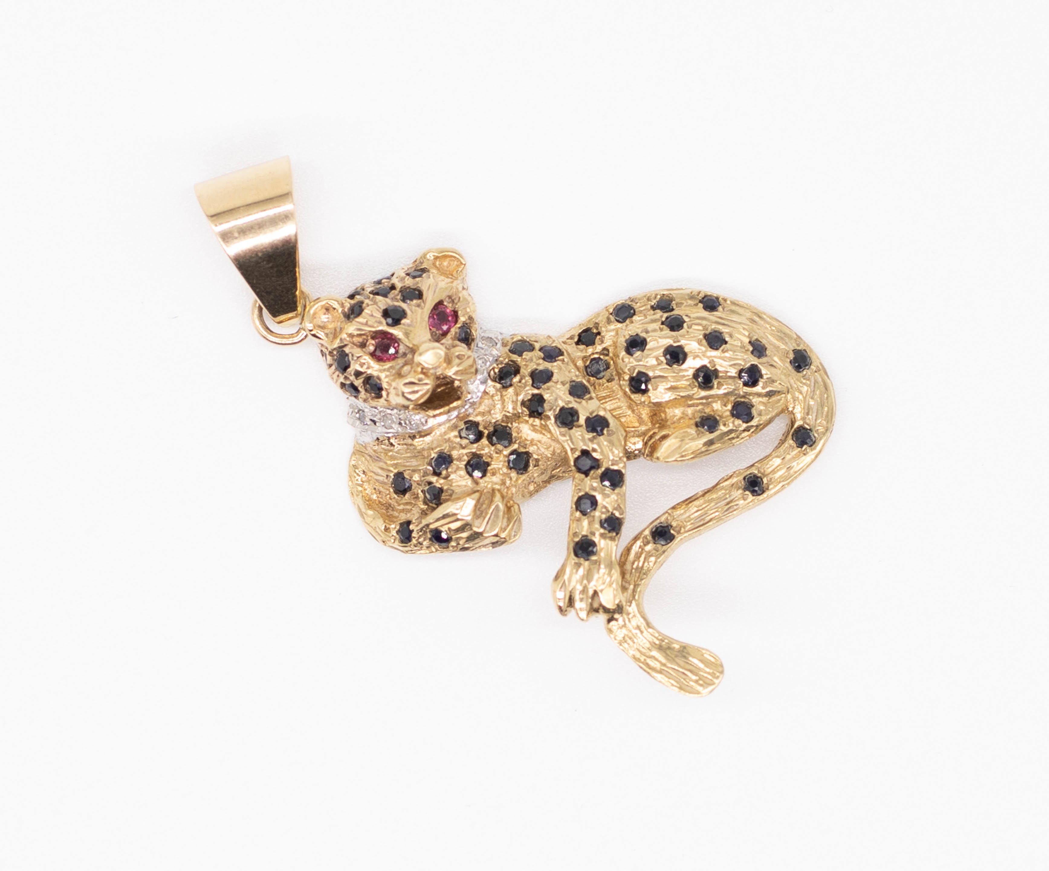 A diamond and sapphire set leopard pendant with ruby eyes, width approximately 35mm. - Image 2 of 2