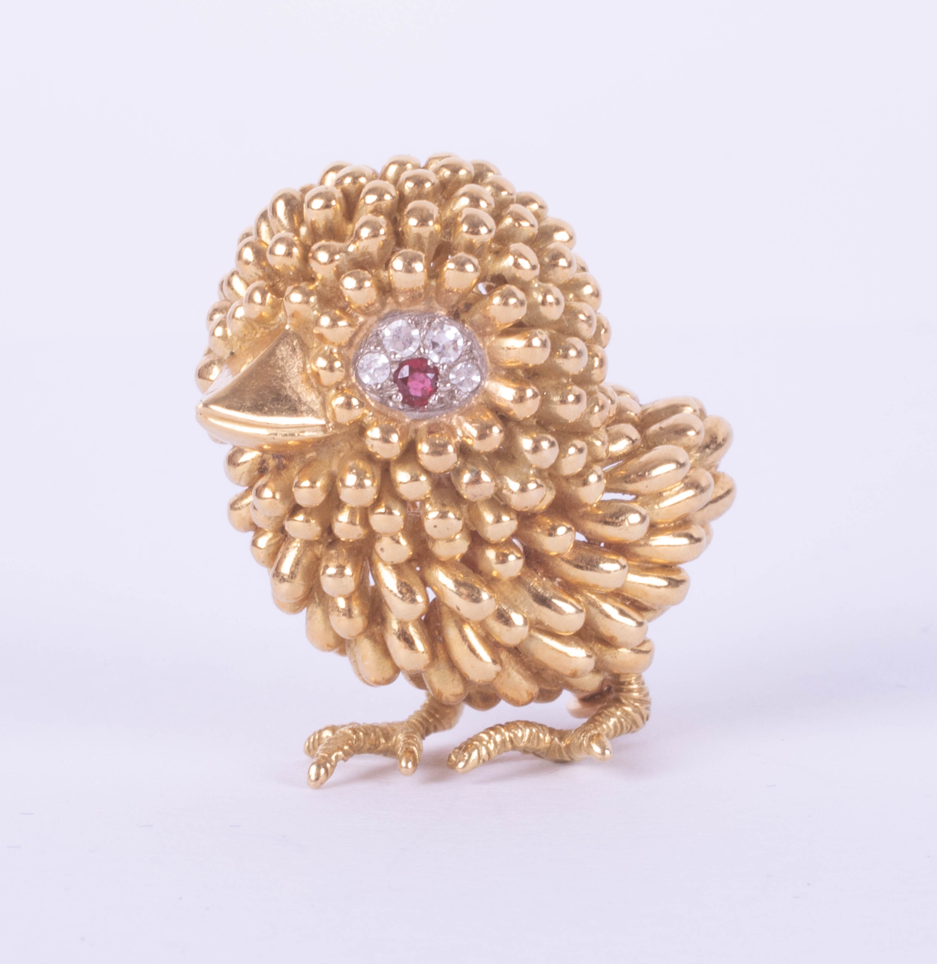 An 18ct gold, ruby and diamond brooch, designed as a chick, the eye mounted with a ruby and with