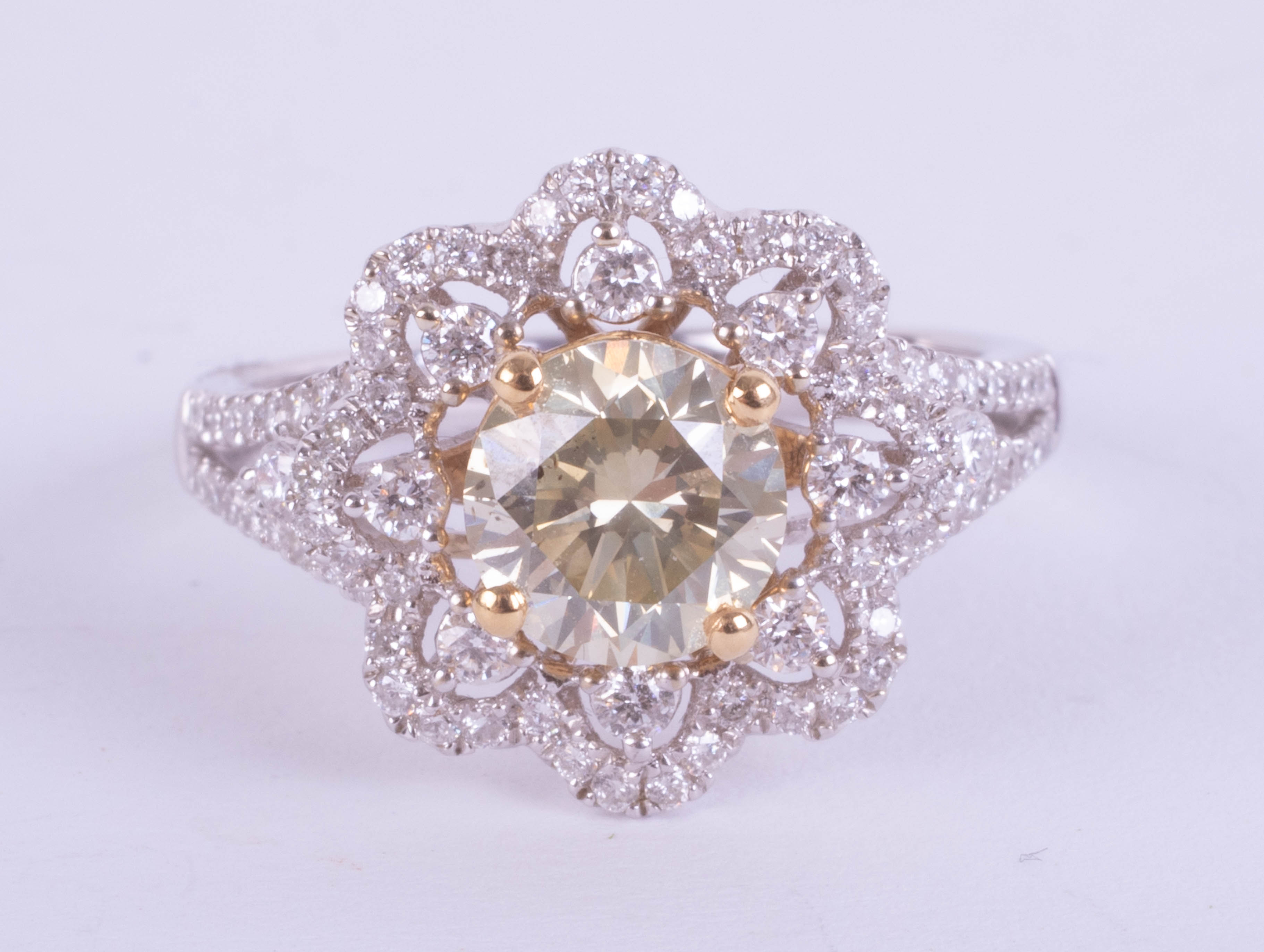 An 18ct white gold daisy-style, ornate dress ring set with a central fancy RBC diamond (1.36ct)