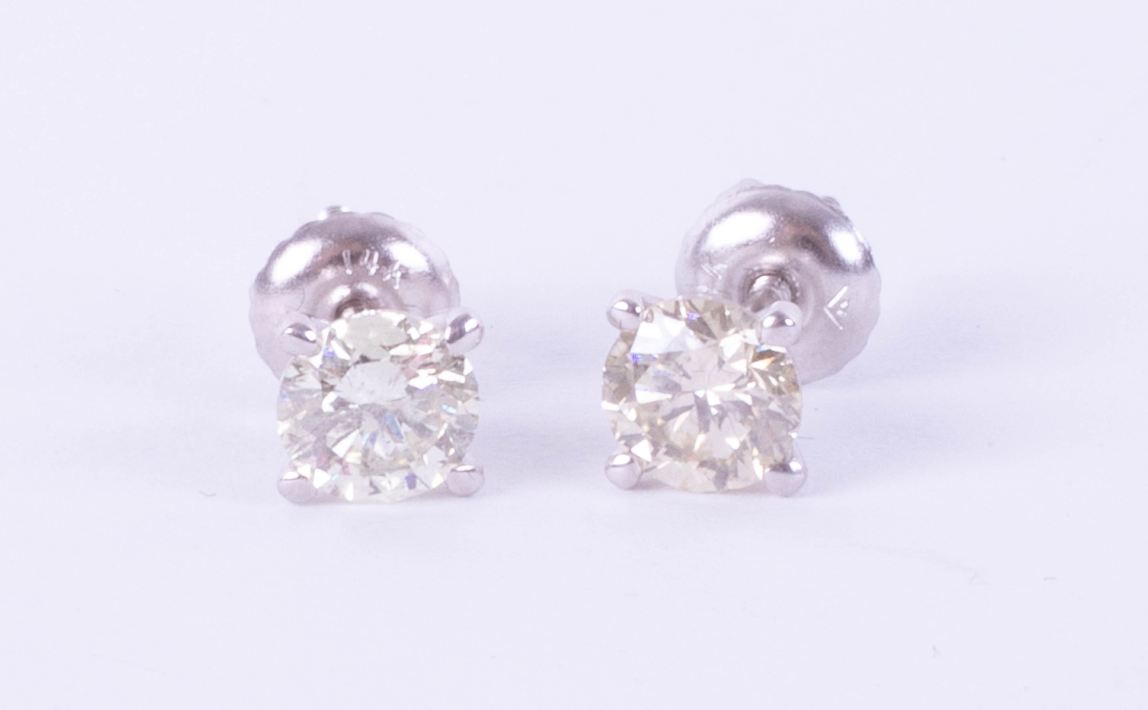 A pair of 14k white gold and diamond earrings, weight 1.09 carat, colour E-F, clarity VS1-VS2