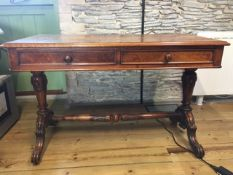 A Victorian walnut library table fitted with two drawers over a stretcher base.