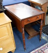 A Victorian mahogany Pembroke table on ring-turned legs fitted with a real and dummy drawers.