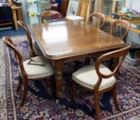 A mahogany dining table with a central insertable extension leaf with original winding handle height