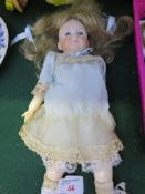 A SIMON AND HALBIG SMALL CHINA HEADED DOLL WITH OPEN GLASS EYES DRESSED IN A VINTAGE DRESS