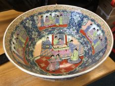 A large circular famille rose style bowl decorated with scrolled figural panels on blue floral