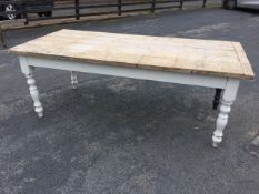 A large rough pine kitchen table with plank top on painted base with turned legs. (84in x 40in x