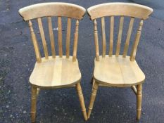 A pair of beech slatback kitchen chairs with solid seats raised on turned legs & stretchers. (2)