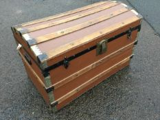 A domed top seamans chest, the trunk mounted with slats on canvas covered ground, having lined
