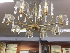 A contemporary brass chandelier supported by chain from ceiling rose, the column with boss