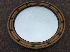 A circular regency style gilt convex mirror, the frame with concave moulding applied with balls,