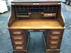 An Edwardian oak rolltop desk, the tambour enclosing pigeonholes and drawers above a frieze drawer