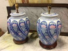 A pair of contemporary chinoiserie tablelamps with pink floral gadrooned moulded jars beneath blue &