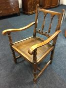 A Derbyshire style oak armchair, the back with spindles having scroll carved shaped arms on turned