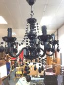 A contemporary black chandelier, with column suspended from ceiling rose having honeycomb moulded