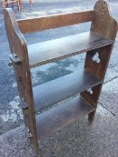 An arts & crafts style oak open bookcase with three pegged shelves, the sides pierced with trefoil