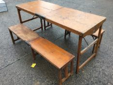 A rectangular Edwardian pine campaign table and two benches by W Thrornhill & Co, the folding