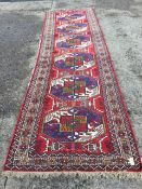 An oriental runner woven with six aztec patterned octagonal geometric medallions on red ground,