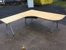A large modern corner office desk with wide rounded work surface having shelf below, raised on