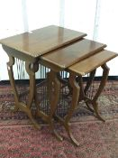 A nest of three mahogany tables with rectangular moulded tops on shield shaped lyre supports with