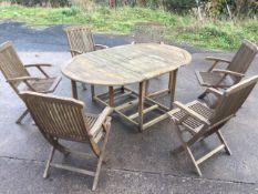 A teak garden suite, the oval slatted table with drop leaves on rectangular frame, the six folding