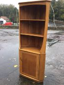 An Ercol oak corner cabinet with shaped apron above illuminated open shelves, with panelled door