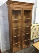 A glazed pine cupboard with moulded cornice above two doors. (40.5in x 13.5in x 75in)