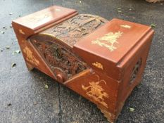 A Chinese carved camphorwood chest, the arched central section profusely carved with battle scenes
