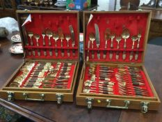 Two cased sets of eastern brass cutlery, the boxes each with trays, the pieces having embossed