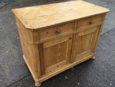 A European pine cabinet with canted corners, having two panelled drawers above panelled cupboards,