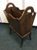 A yew magazine rack, the tapering box with two divisions on splayed legs, the sides with pierced