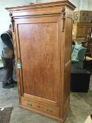 A Victorian pitch pine wardrobe with moulded cornice above a wide panelled door enclosing hanging