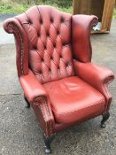 A Queen Anne style button upholstered wing armchair with brass studding, raised on cabriole legs.