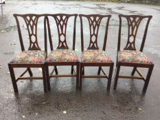 A set of four mahogany Chippendale style dining chairs with pierced splats above floral
