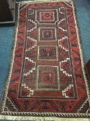 An oriental belouchi rug woven with four square panels of geometric designs framed by zig-zag